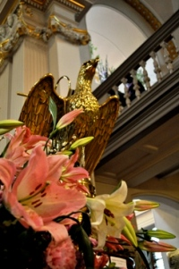 pink lilies in front of brass eagle